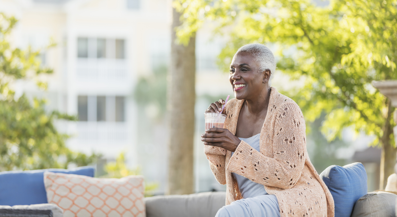 A senior African-American woman in her 60s relaxing outdoors on her patio, sipping a cold, refreshing beverage through a straw.