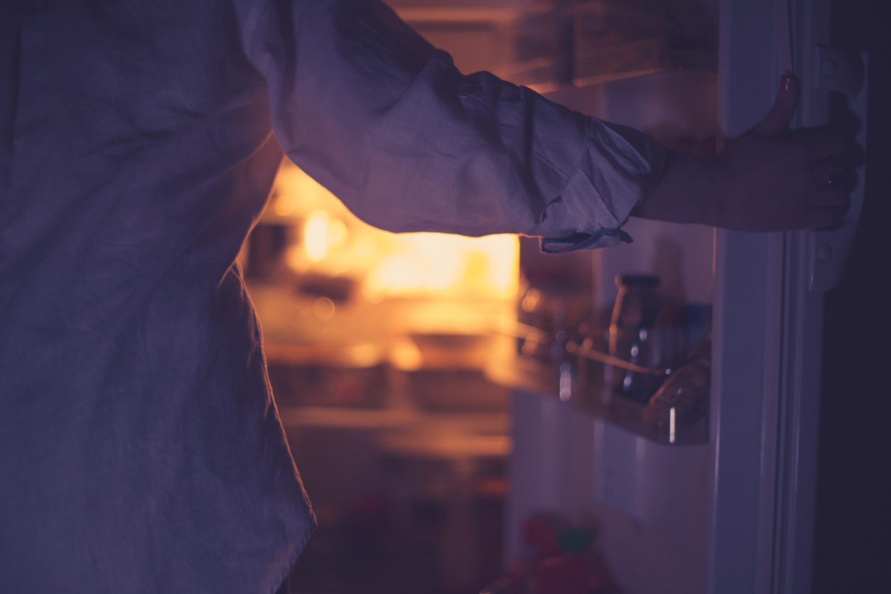 Close-up of woman holding the open refrigerator door during the night